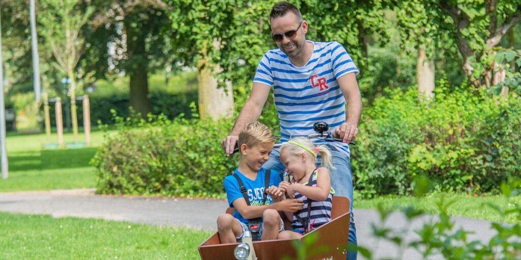 Cargobike mit einem Mädchen und einem Jungen besetzt und der Vater pedalt durch einen Park